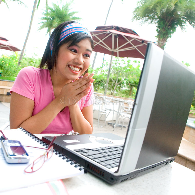 Excited young student with laptop. Young Asian student showing excitement while using her laptop royalty free stock photos