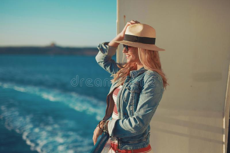 Happy young traveler woman on cruise ship waiting for docking stock photography