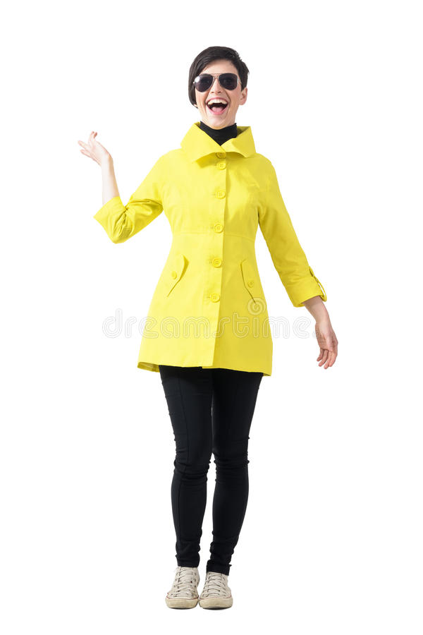 Excited young trendy woman in yellow raincoat. stock images