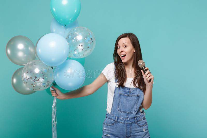 Excited young woman in denim clothes sing song in microphone, celebrating and holding colorful air balloons isolated on. Blue turquoise wall background stock photography