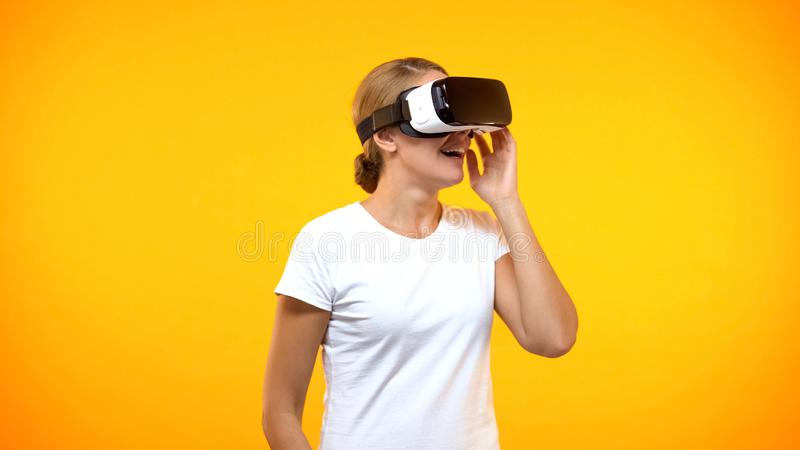 Excited young woman enjoying virtual reality wearing game headset, entertainment royalty free stock image
