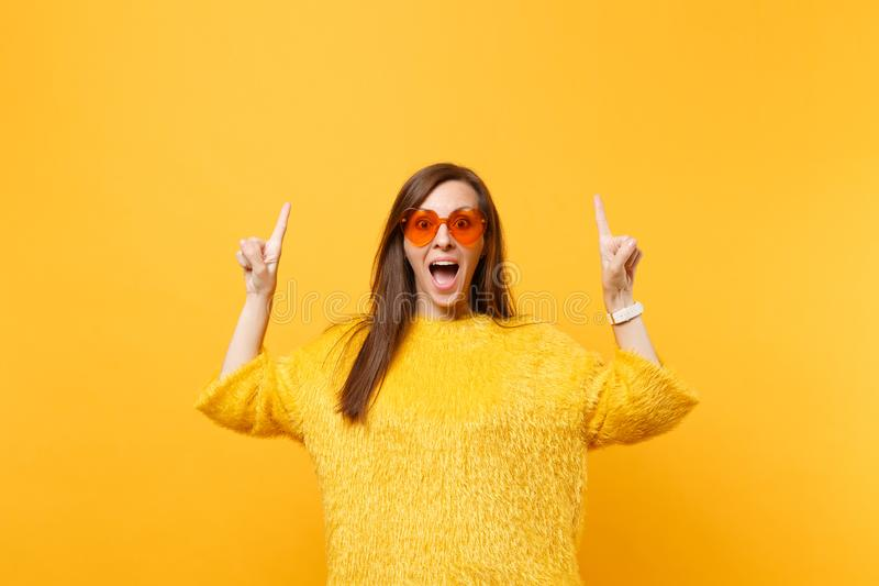 Excited young woman in fur sweater and heart orange glasses pointing index fingers up on copy space isolated on bright. Yellow background. People sincere stock images