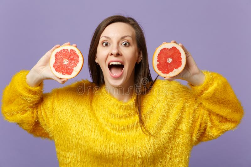Excited young woman in fur sweater keeping mouth open holding halfs of fresh ripe grapefruit isolated on violet pastel royalty free stock photos