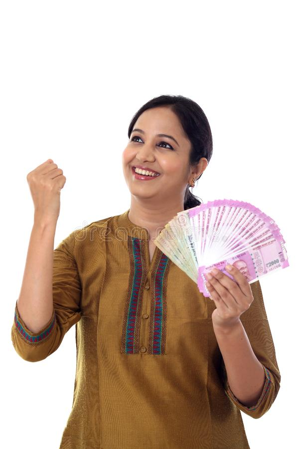 Excited young woman holding Indian 2000 rupee notes stock image