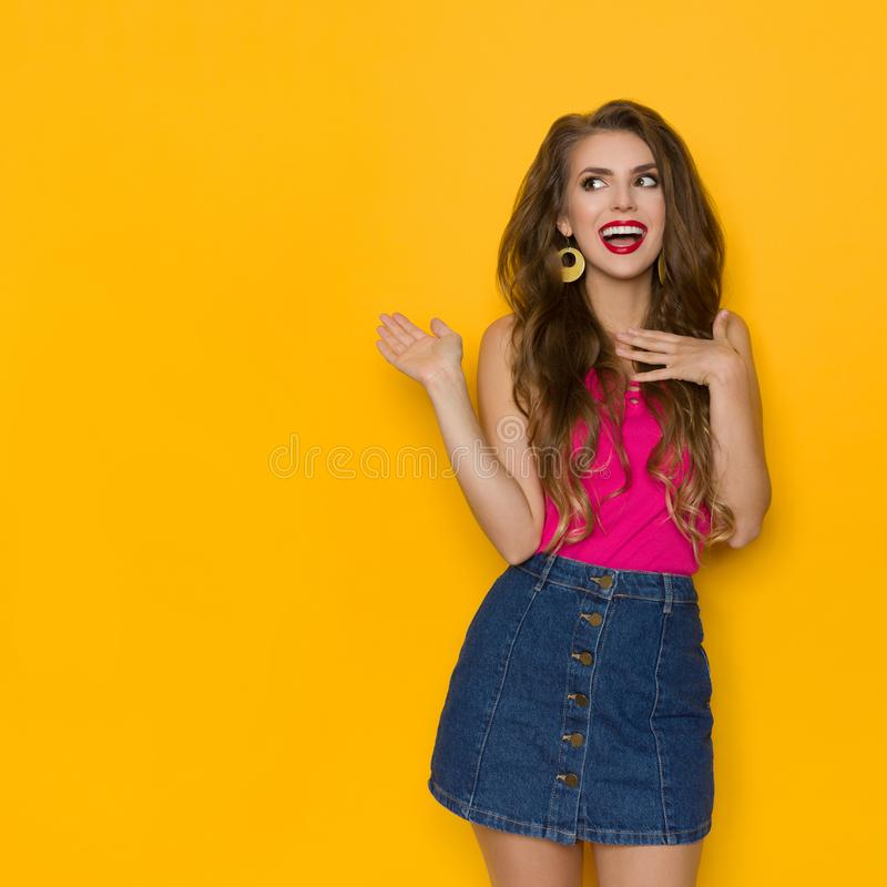 Excited Young Woman In Jeans Mini Skirt And Pink Top Is Holding Hand On Chest. Looking away and gesturing. Three quarter length studio shot on yellow royalty free stock image