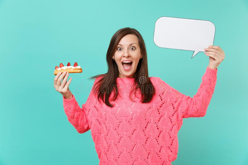 Excited young woman in knitted pink sweater holding eclair cake, empty blank Say cloud speech bubble for promotional. Content isolated on blue background royalty free stock photography
