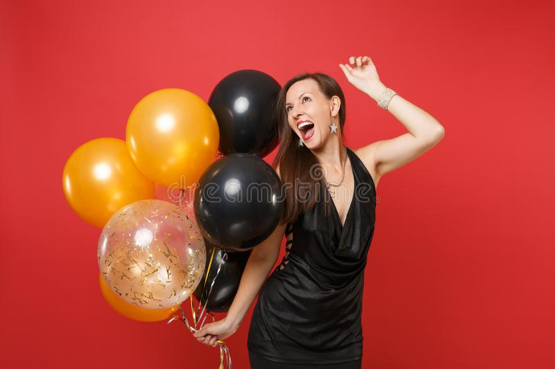 Excited young woman in little black dress celebrating, rising hand, holding air balloons on red background stock photos