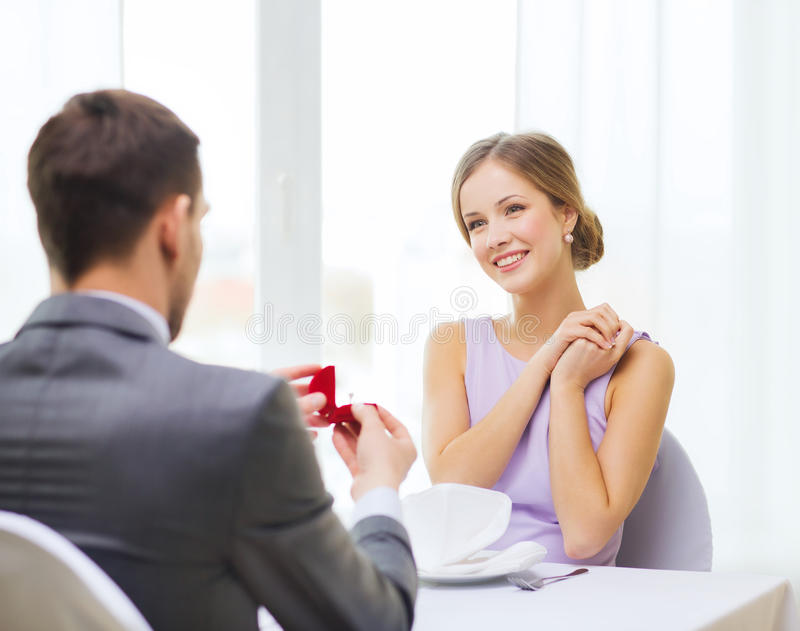 Excited young woman looking at boyfriend with ring