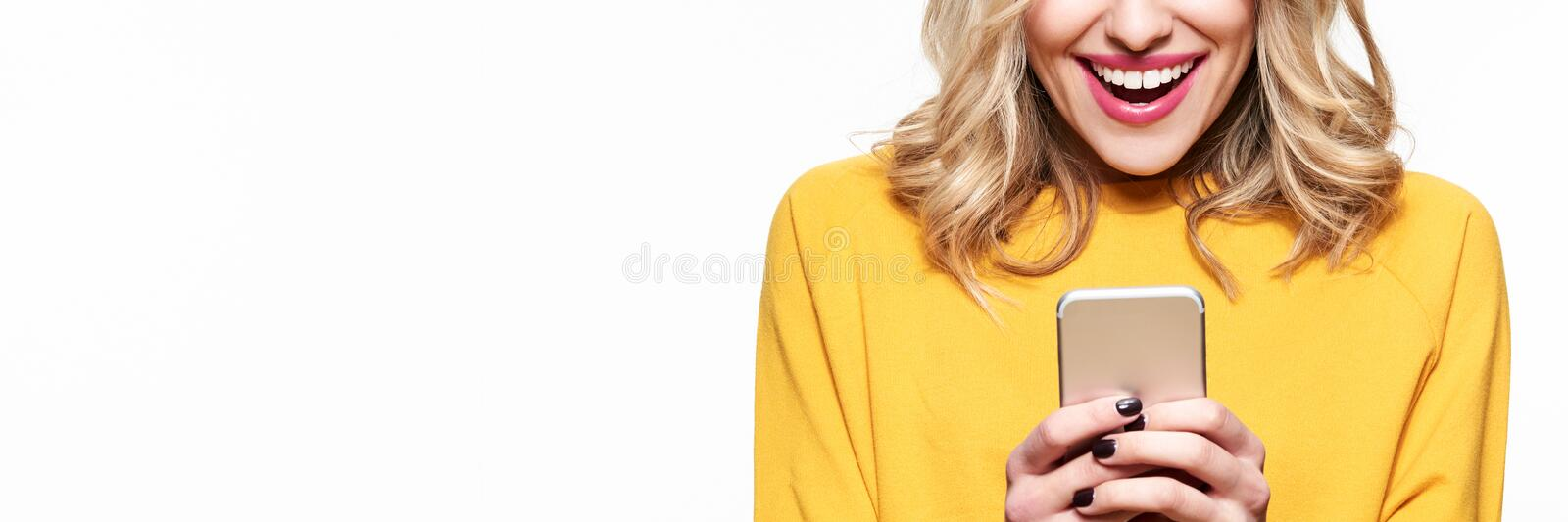 Excited young woman looking at her mobile phone smiling. Woman reading text message on her phone. royalty free stock photography