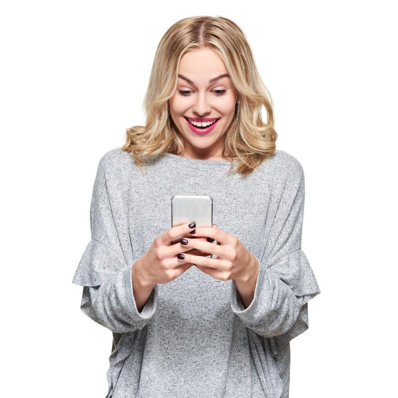 Excited young woman looking at her mobile phone smiling. Woman reading text message on her phone, isolated over white background. Excited young woman looking at stock images