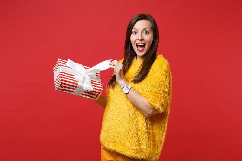 Excited young woman with opened mouth hold red striped present box with gift ribbon isolated on red background stock photography