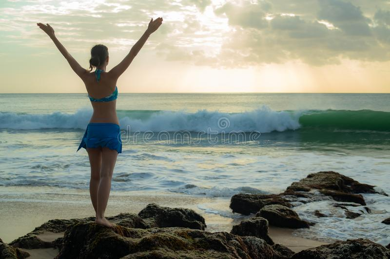 Excited young woman raising arms at the beach in front of the ocean. View from back. Sunset at the beach. Bali, Indonesia royalty free stock photo