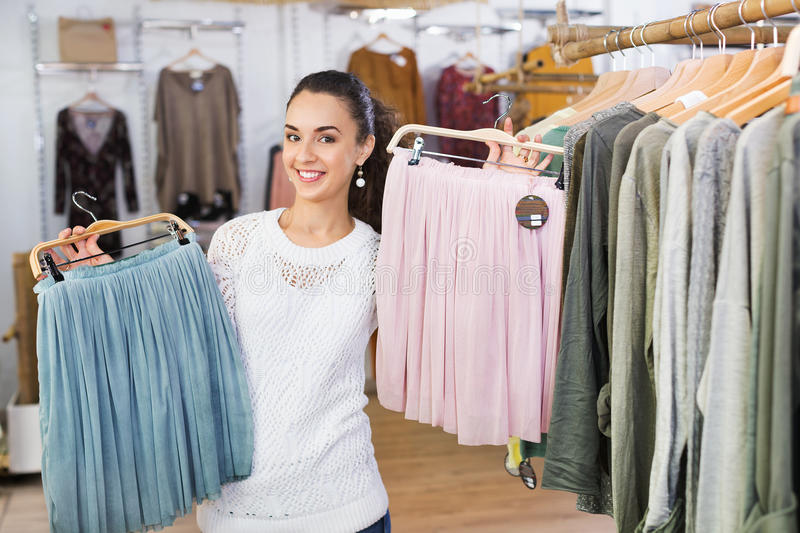 Excited young woman shopping skirts stock images
