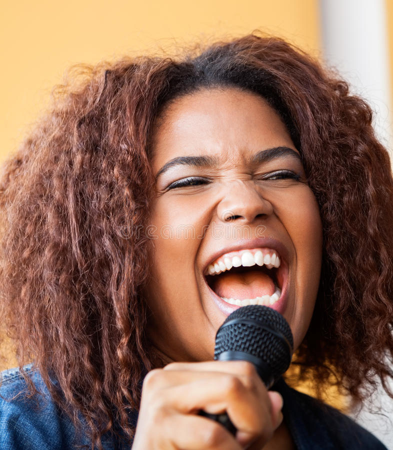 Excited Young Woman Singing While Holding stock images