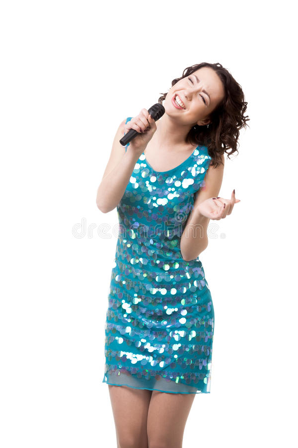 Excited young woman singing in short sparkling blue dress stock image