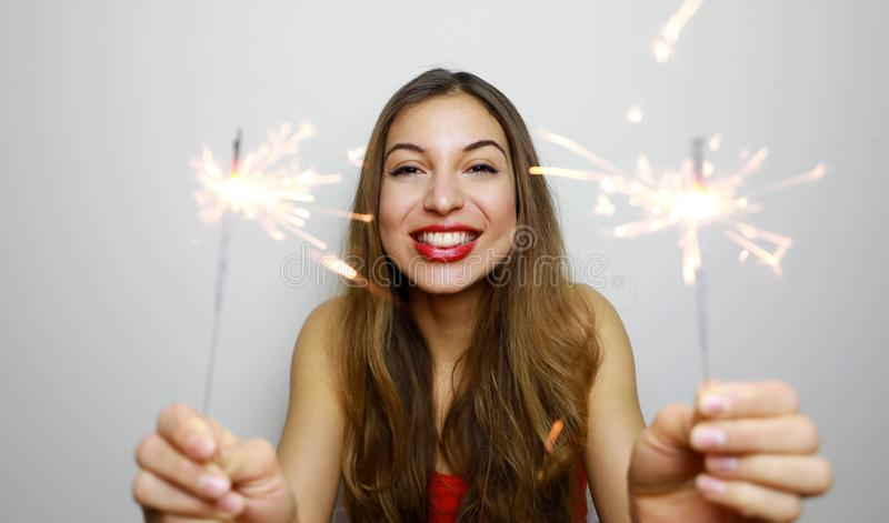 Excited young woman with sparklers laughing on white background. Indoor photo of happy long-haired girl celebrating new year with stock photo
