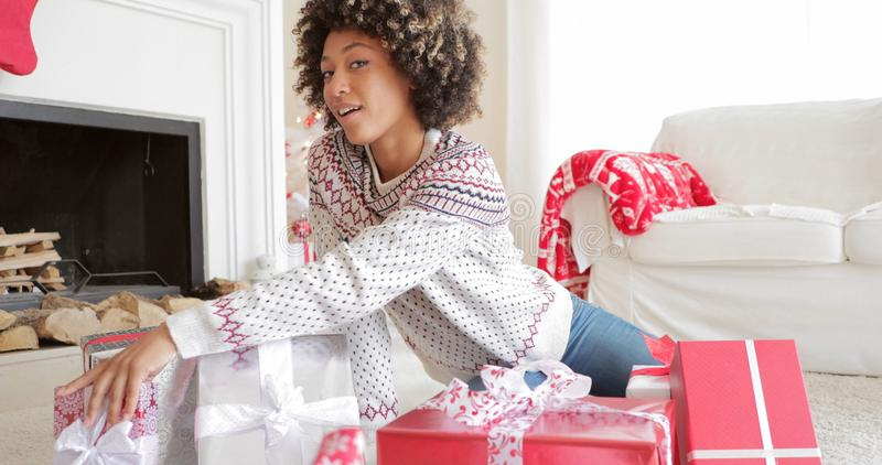 Excited young woman unwrapping her Christmas gifts stock photos