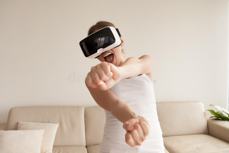 Woman in VR goggles enjoying 3d gaming at home royalty free stock image