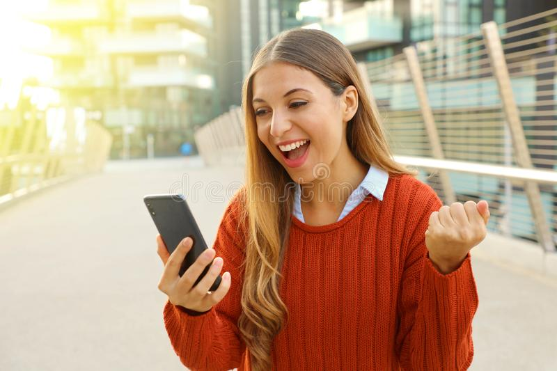 Excited young woman watching her phone in the street. Winning girl celebrating with mobile in her hand outside stock photo