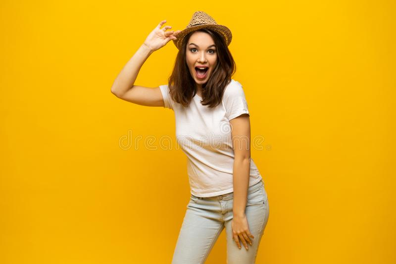 Excited young woman in white t-shirt, widely smiling, looking at camera. Isolated on yellow background royalty free stock photos