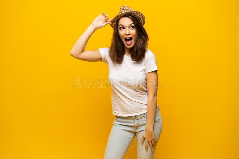 Excited young woman in white t-shirt, widely smiling, looking at camera. Isolated on yellow background royalty free stock photo