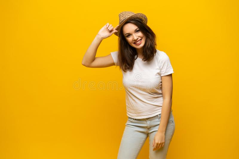 Excited young woman in white t-shirt, widely smiling, looking at camera. Isolated on yellow background stock photography