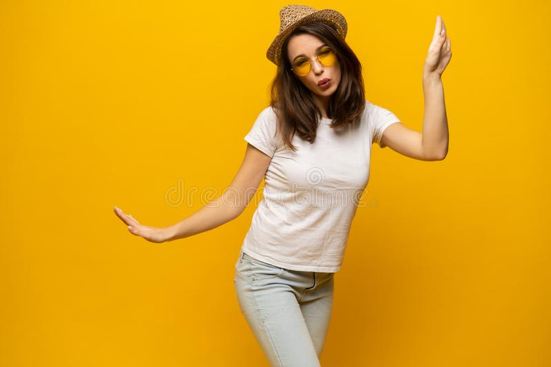 Excited young woman in white t-shirt, widely smiling, looking at camera. Isolated on yellow background royalty free stock image