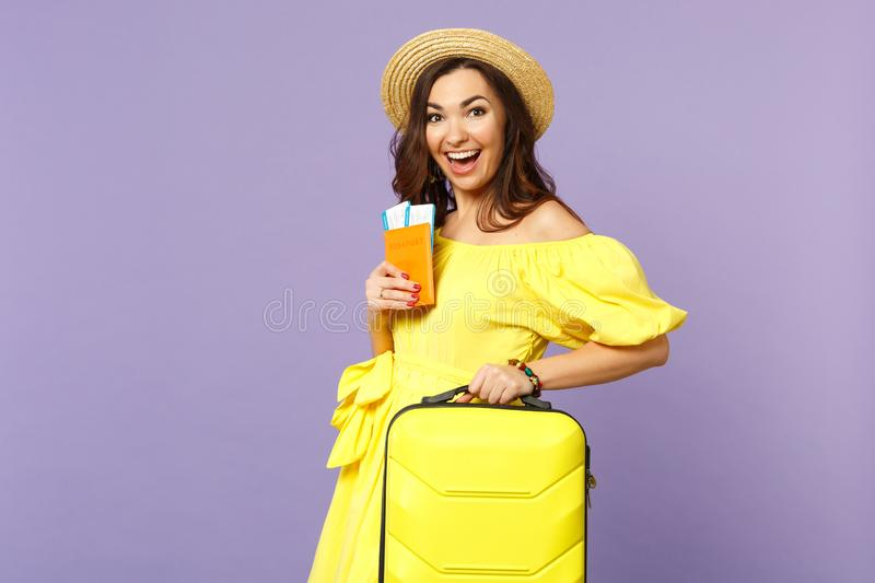 Excited young woman in yellow dress, summer hat hold suitcase, passport boarding pass ticket isolated on pastel violet stock photography