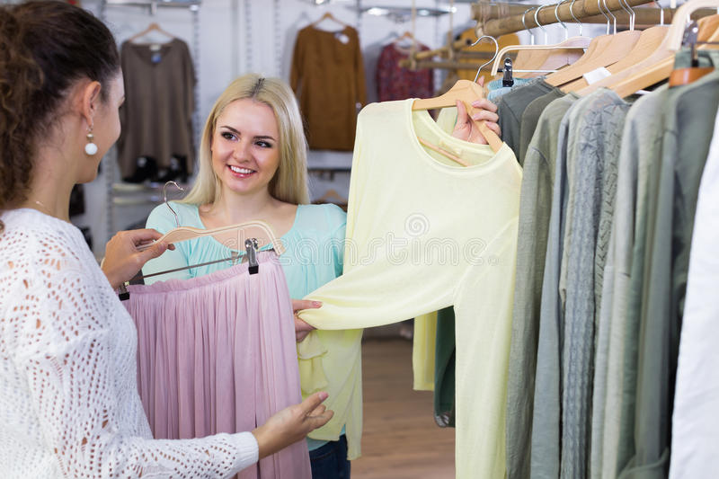 Excited young women choosing pullover and skirt stock photography