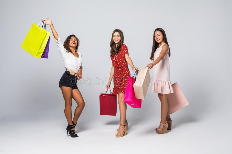 Excited young women with colorful shopping bags posing isolated on white background stock photos