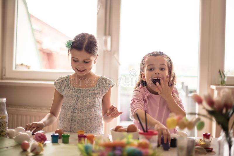 Excitement for Easter. Little girls coloring Easter egg royalty free stock photography