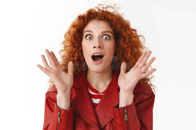 Excitement, surprised emotions concept. Astonished wondered redhead curly-haired attractive female drop jaw screaming. Amazed widen eyes impressed raise hands stock photography
