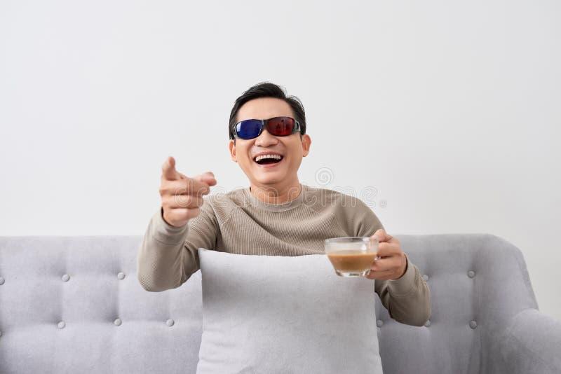 Exciter l'affichage à cristaux liquides tridimensionnel TV de montre de jeune homme avec le verre d'oeil dans un salon photo stock