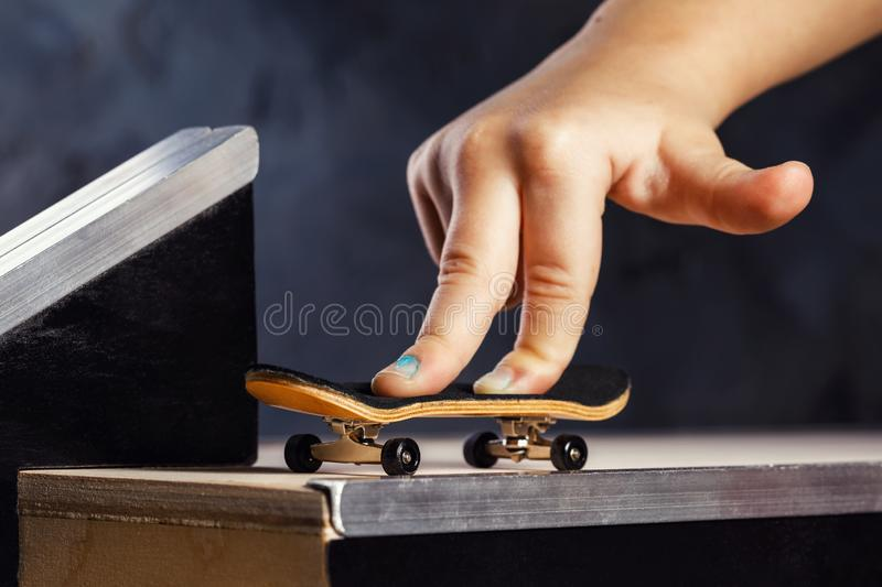 An exciting activity for a child, riding a mini skateboard or fingerboard on a specially equipped track royalty free stock photography