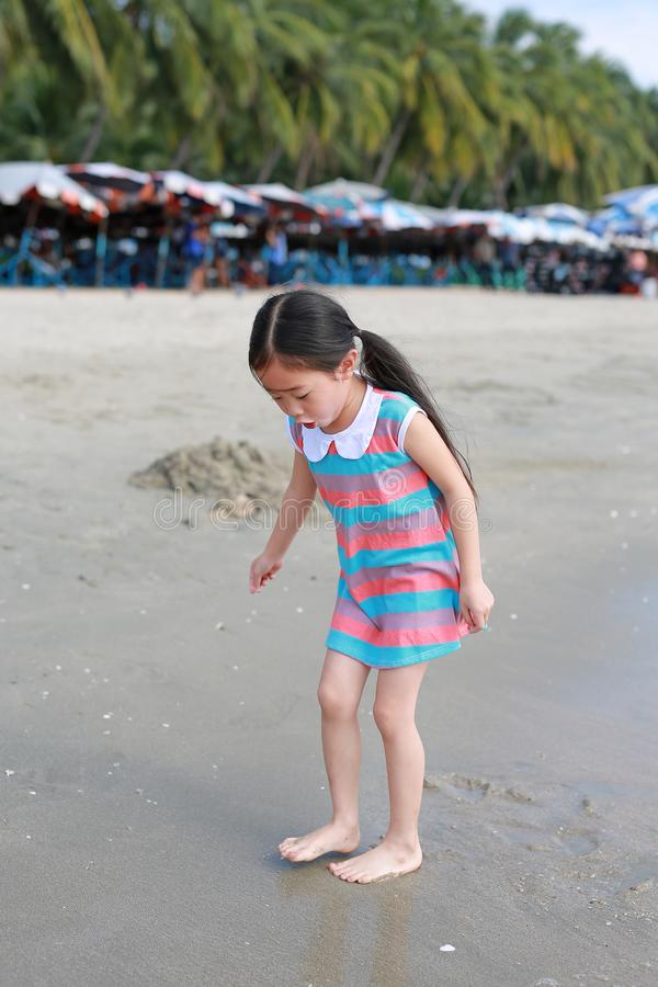 Exciting Asian child girl while come to play sand and sea at the beach on holiday stock photography