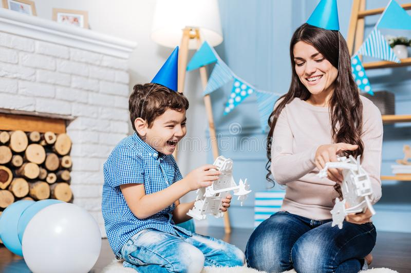 Happy son playing with toy robots with his mother royalty free stock image