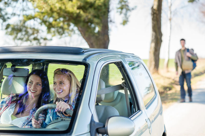 Exciting girls drive car taking hitch-hiker royalty free stock photo