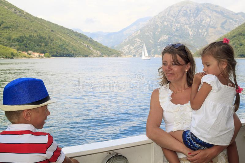 Exciting journey with children. happy mother with her son and da. Ughter in her arms cross the magnificent Bay of Kotor on the ferry, sea, adriatic, lifestyle stock image