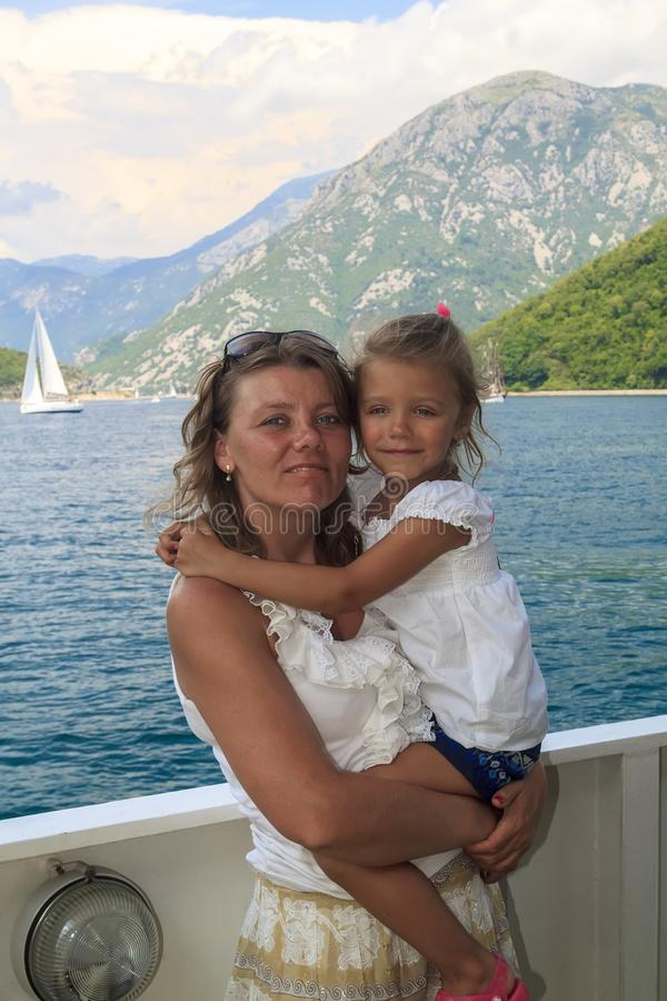 Exciting journey with kid. happy mother with her daughter in her. Arms cross the magnificent Bay of Kotor on the ferry, sea, adriatic, lifestyle, montenegro royalty free stock photography