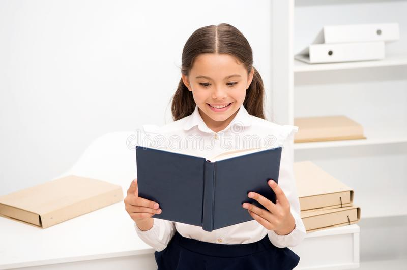 Exciting literature concept. Girl child read book stand white interior. Schoolgirl studying textbook. Kid girl school royalty free stock photos