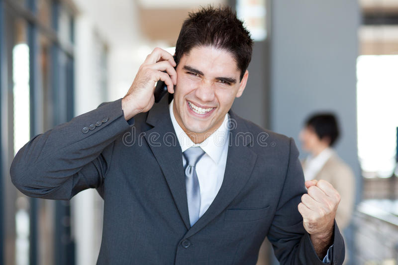 Exciting news. Young businessman talking on cell phone and receive exciting news royalty free stock image