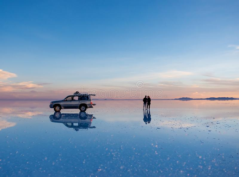 Exciting scenery of spacious Salar de Uyuni with couple and car. Reflection on mirror surface royalty free stock photography