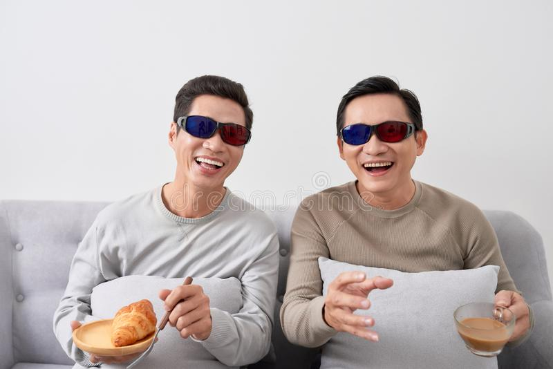 Exciting young man watch three-dimensional LCD TV with eye glass in a living room royalty free stock image