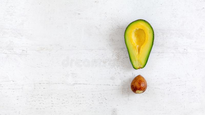 Exclamation mark made of avocado half and seed, on white board, photo from above. Wide banner with space for text on left side.  royalty free stock photos
