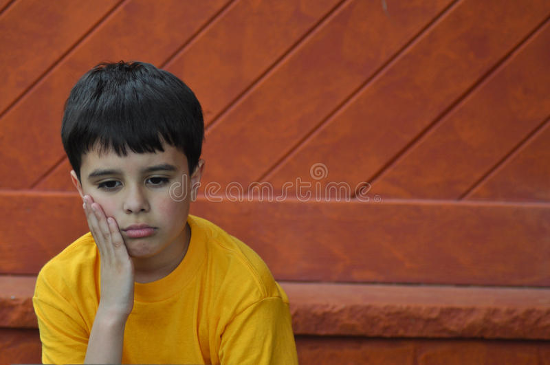 Excluded Boy. Sad little child feels alone during the recess time, at elementary school. Available space to insert text stock image