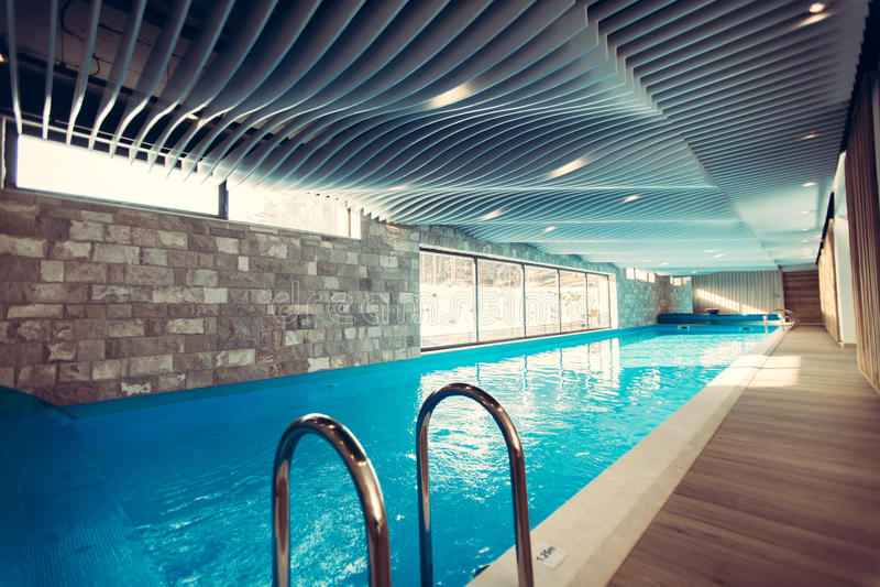 Exclusief zwembad in een wellnesshotel Het binnen zwembad van de luxetoevlucht met mooi schoon blauw water royalty-vrije stock foto
