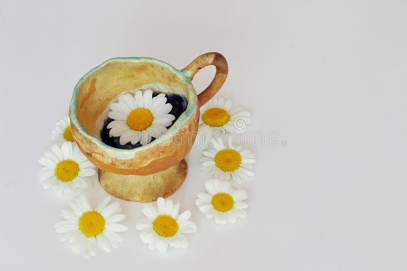 Exclusive ceramic tea cup decorated with icing in circle of field daisies on light background. Symbolic concept — summer, sun,. Beautiful bright stock image