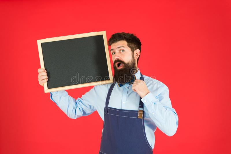 Exclusive cocktail. Man bearded bartender or cook in apron hold blank chalkboard. Price list concept. Hipster bartender. Show blackboard copy space. Hipster stock photo