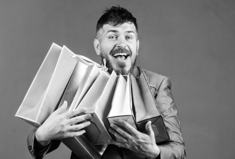 Exclusive commercial offer. Man bearded businessman customer carry many shopping bags. Enjoy shopping profitable deals royalty free stock photo