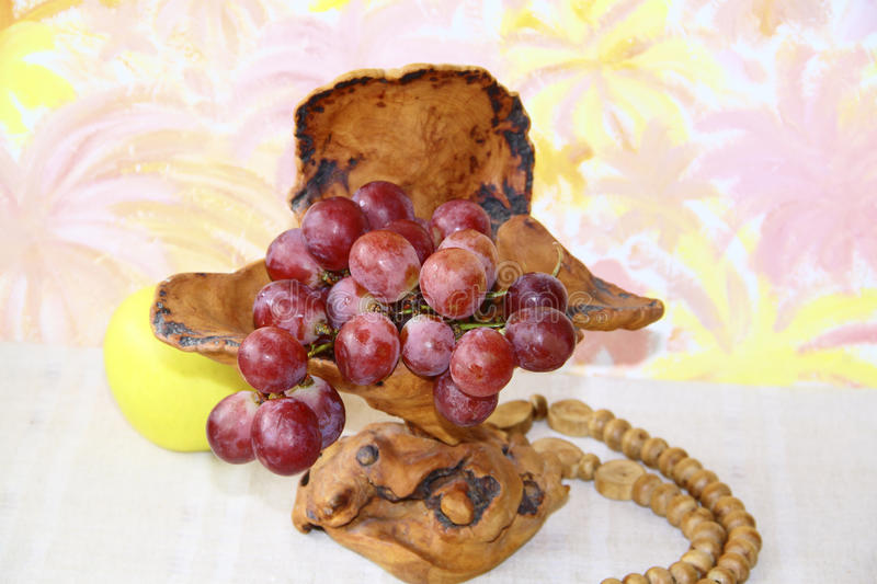 Exclusive wooden vase with pink grapes royalty free stock photo
